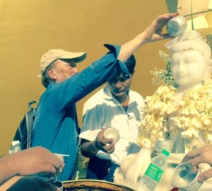 Neville pouring water over Buddha in a Bagan temple, Myanmar to celebrate his birth day of Saturday