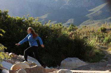 Woman running in mountains wearing compresslite packaway jacket